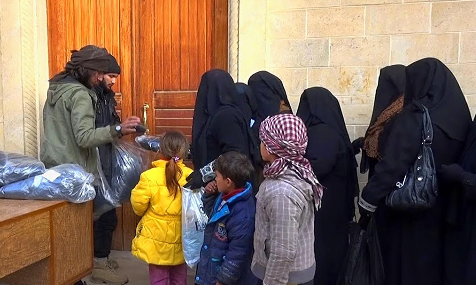 عنصرين من التنظيم يوزعون النقاب على نساء الموصل (أسوشيتد برس)