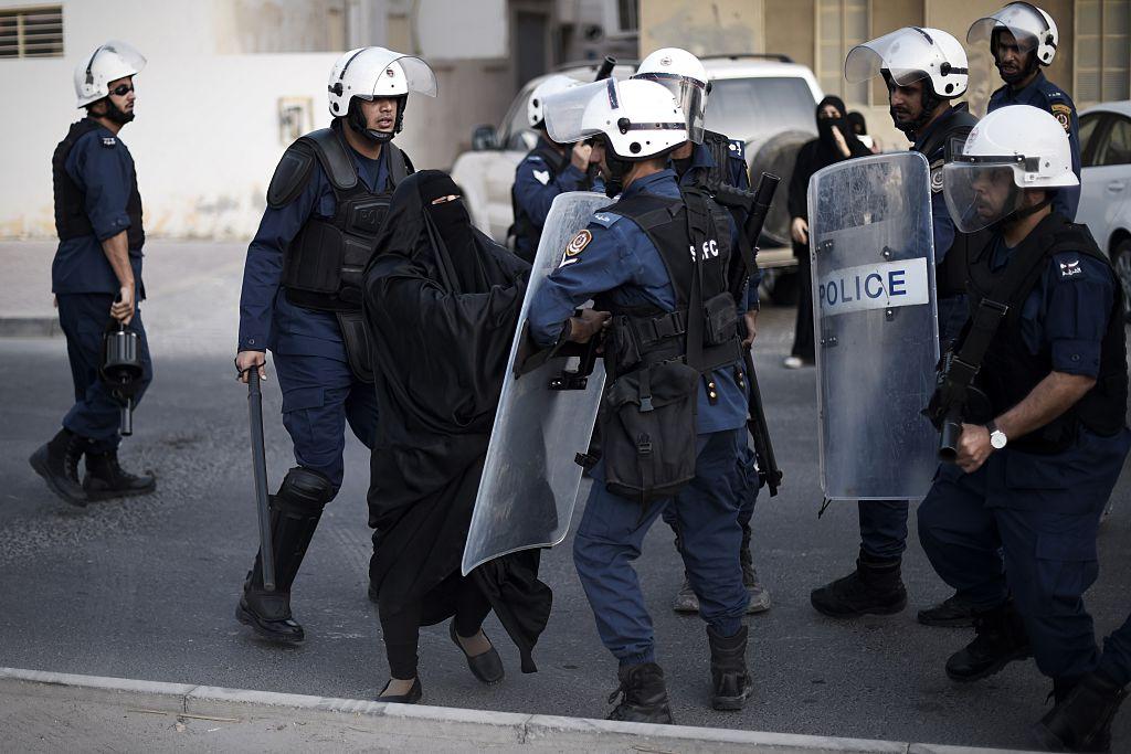 قوات شرطة بحرينية تعتدي على امرأة بعد فض تظاهرة في 2015 (محمد الشيخ/ أ.ف.ب)