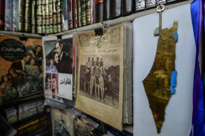 يد في ألمانيا تقلّب على الشاشة كتابًا في سوريا